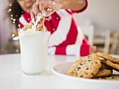 Mädchen taucht Cookie in Milchglas