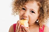 Mixed race girl eating apple