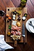 Assorted antipasti on a wooden board (view from above)