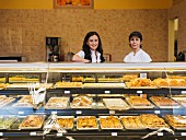 Staff behind a glass counter with pastries