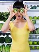 Frau hält sich halbierte Kiwi vor Augen