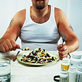 Overweight man eating plate full of pills