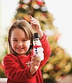 Caucasian girl holding snowman Christmas ornament