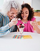 Grandmother and granddaughter sharing ice cream sundae