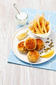 Fishcakes with peas, chips and a cream dip