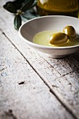 Green olives in a bowl with olive oil