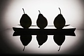 Black silhouettes of pears on a plate, and reflection