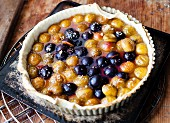 Plum and greengage tart on a baking tray