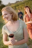 Friends Strolling with Wine Through Vineyard
