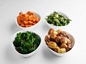 Side dishes of steamed vegetables and roast potatoes.