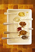 Assorted spices on spoons sitting in flour