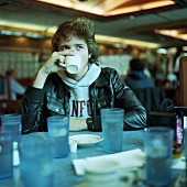 Young man drinking coffee at diner