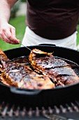 Fish in Cast Iron Pan Being Basted and Cooked on Grill