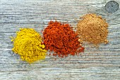 Three mounds of different spices from above