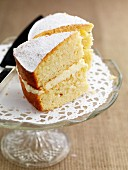 Two slices of gluten-free lemon sponge cake with icing sugar