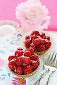Two strawberry tartlets and cake forks on a floral tablecloth