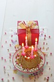 A birthday cake with four burning candles and a gift-wrapped present with a bow