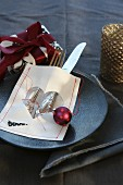 Christmas place setting with sewn parchment cutlery bag, tree bauble and wrapped present
