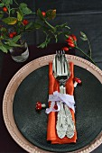 Place setting with linen napkin, ribbon napkin ring, decorative fly agaric mushrooms and rosehips