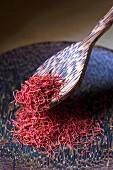 Safranfäden auf Teller mit Holzlöffel