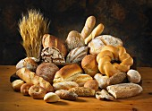 Various types of bread and rolls with ears of wheat on a wooden table