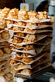 Lots of coconut macaroons, stacked on grease-proof paper