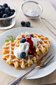 Waffles with icing sugar, blueberries, cream and fruit sauce