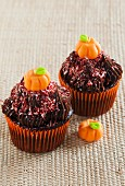 Two chocolate Halloween cupcakes decorated with fondant pumpkins