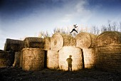 Person Running Across Top of Large Hay Bales and Shadow