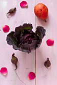 A red cabbage, a pear, beetroot and rose petals