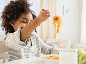 An African-American boy eating spaghetti