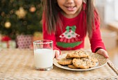 A girl setting milk and cookies on the table for Santa Claus
