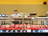 A sales assistant behind a meat counter
