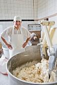 Bäcker an Knetmaschine in einer Bäckerei
