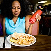A woman squirting ketchup onto a plate of fast food