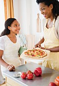 A mother and daughter making pizza
