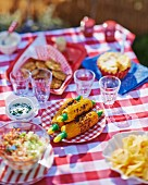 A garden table laid with grilled corn on the cob, salad, crisps and apple pie