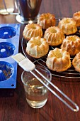 Mini Bundt cakes on a wire rack next to the baking mould