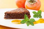 A slice of chocolate cake with kaki sauce