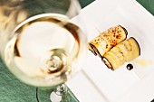 Gebratene Auberginenröllchen und ein Glas Weisswein