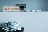 Stapel mit vieleckigen Tellern, darüber ein mit Papierschiffchen und nordischen Malereien dekorierter Absatz