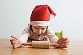 A little girl wearing a Santa hat sitting at a table with a rolling pin