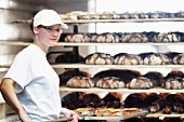 A young baker pushing a tray of freshly baked loaves onto a shelf