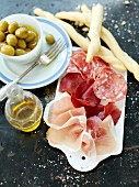 Ham and salami with olives and grissini