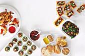 Verschiedenes Fingerfood: Garnelen, Gurkentaler, Knoblauch-Oliven und Dukkah mit Olivenöl und knusprigem Brot