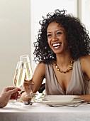 Junge Frau trinkt ein Glas Sekt im Restaurant