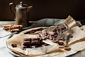 Dark chocolate, chocolate beans and spices with vintage teapot