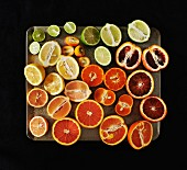 Variety of Sliced Citrus Fruit on Tray, High Angle View