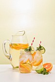 White Wine Sangria in Pitcher and Two Mason Jars with Fruit Garnishing