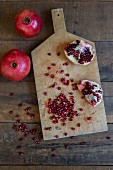Sliced Pomegranate and Seeds on Cutting Board next to Whole Pomegranates